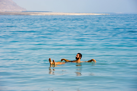 dead sea: DEAD SEA; ISRAEL - 16 OCTOBER, 2014: A man floating in the salty water of the dead sea in Israel Editorial