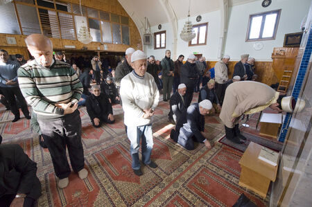 coran: ENSCHEDE, THE NETHERLANDS - FEB 13, 2015: Muslims are standing and bowing during the friday afternoon prayer in a mosque in the Netherlands
