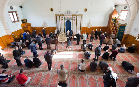 islamic pray: ENSCHEDE, THE NETHERLANDS - FEB 13, 2015: Muslims are standing and bowing during the friday afternoon prayer in a mosque in the Netherlands