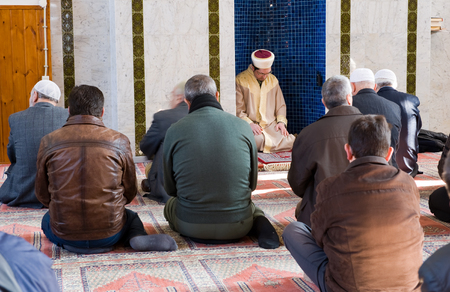 coran: ENSCHEDE, THE NETHERLANDS - FEB 13, 2015: An imam is sitting and praying in a mihrab during the friday afternoon prayer in a mosque in the Netherlands