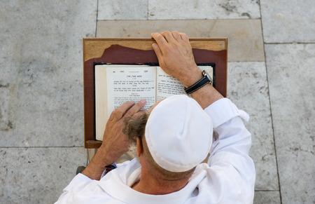 JERUSALEM, ISRAEL - OCT 08, 2014: An jewish man is reading in the torah near the wailing wall in Jerusalem Editorial