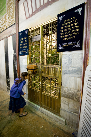 leah: HEBRON, ISRAEL, 10 OCT, 2014: A young girl is watching through the bars of an iron door to the tomb of patriarch Abraham. The tombs of the patriarchs are situated in the Cave of Machpelah in Hebron Editorial