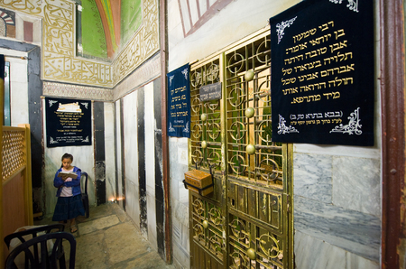 leah: HEBRON, ISRAEL, 10 OCT, 2014: A young girl is reading the torah close to the tomb of patriarch Abraham behind the green iron doors. The tombs of the patriarchs are situated in the Cave of Machpelah in Hebron Editorial