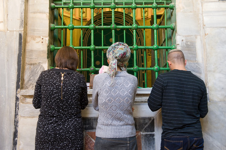 leah: HEBRON, ISRAEL, 10 OCT, 2014: Three jewish people are praying in front of the tomb of patriarch Abraham. The tombs of the patriarchs are situated in the Cave of Machpelah in Hebron