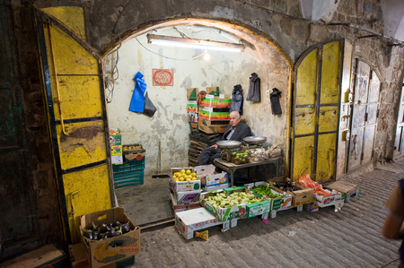 greengrocer: HEBRON, ISRAEL - 10 OCT, 2014: An elderly man sitting in his small fruit and greengrocer Editorial