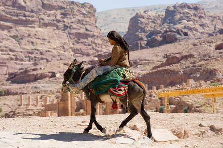 east riding: PETRA,  JORDAN - OCT 12, 2014: A donkey with his owner on his horseback riding in Petra in Jordan