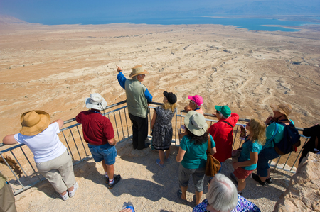 travel guide: MASADA, ISRAEL - OCT 14, 2014: A guide gifts an explanation about Masada to tourists