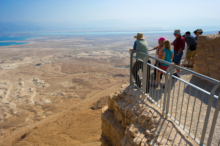 MASADA, ISRAEL - OCT 14, 2014: Tourists enjoying the view from Masada