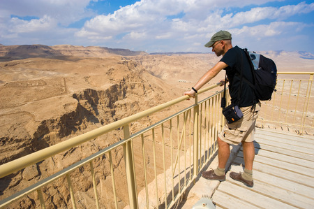 MASADA, ISRAEL - OCT 14, 2014: A tourist is enjoying the view from the lower terrace of the palace of king Herod on the rock Masada in Israel
