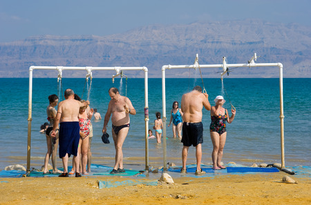 coastal erosion: DEAD SEA, ISRAEL - OCT 13, 2014: People are taking a shower after they floated in the water of the dead sea in Israel Editorial