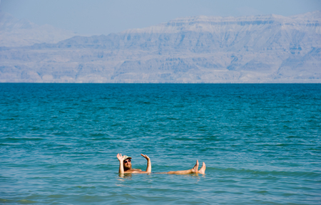 dead sea: DEAD SEA, ISRAEL - OCT 13, 2014: A man is floating in the water of the dead sea in Israel Editorial