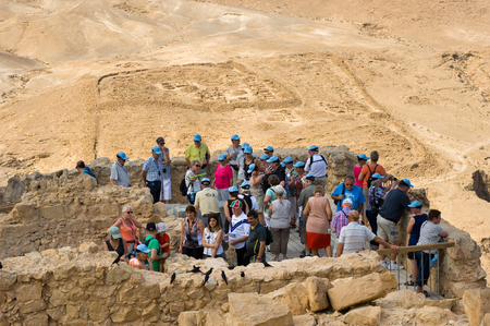 masada: MASADA, ISRAEL - OCT 14, 2014: Tourists on top of the rock Masada in Israel, with a Roman camp on the background Editorial