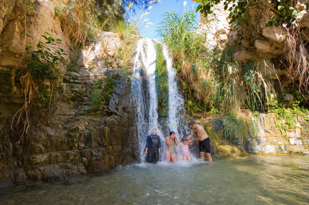 nature reserves of israel: EIN GEDI, ISRAEL - OCT 15, 2014: Children and a man are playing in one of the waterfalls of the oasis Ein Gedi close to the dead sea in Israel