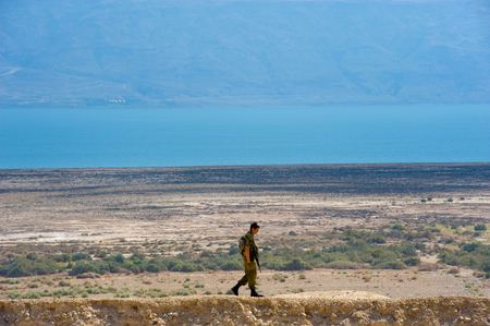 middle east peace: DEAD SEA, ISRAEL - OCT 15, 2014: Israelien soldier walking alone on a hill in front of the dead sea in Israel close to Qumran