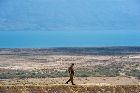 soldado: Mar Muerto, Israel - 15 de octubre 2014: Soldado isra�lien caminando solo en una colina frente al mar muerto en Israel cerca de Qumran