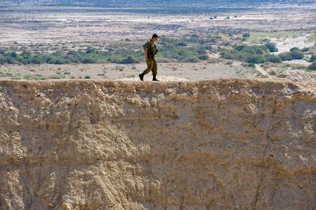 israel war: DEAD SEA, ISRAEL - OCT 15, 2014: Israelien soldier walking alone on a hill in front of the dead sea in Israel close to Qumran
