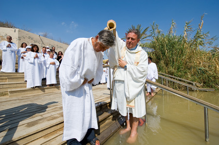 bautismo: Jeric�, ISRAEL - 15 de octubre 2014: Un hombre est� siendo bautizado por el agua durante un ritual del bautismo en Qasr el Yahud cerca de Jeric� en el r�o Jord�n