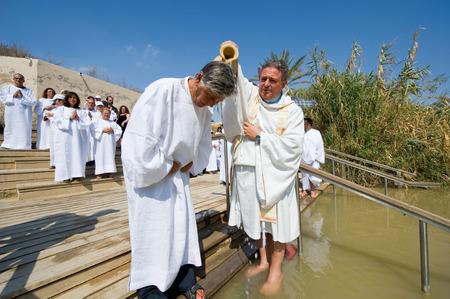 baptized: YERICHO, ISRAEL - OCT 15, 2014: A man is being baptized by water during a baptism ritual at Qasr el Yahud near Yericho on the Jordan river