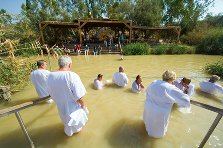baptismal: YERICHO, ISRAEL - OCT 15, 2014: Religious christians with white clothes going into the water of the Jordan river at baptismal site Qasr el Yahud near Yericho