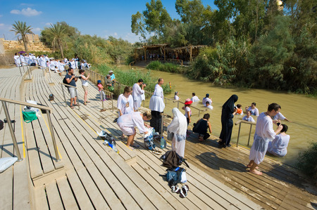 baptize: YERICHO, ISRAEL - OCT 15, 2014: Religious christians with white clothes going into the water of the Jordan river of baptismal site Qasr el Yahud near Yericho