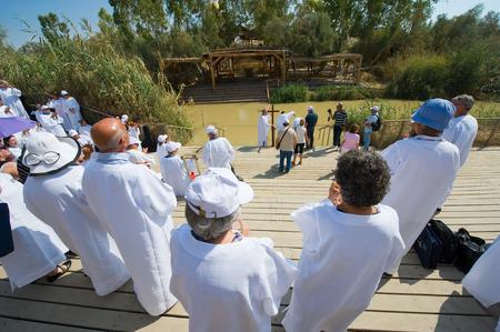 battesimo: Gerico, Israele - 15 ottobre 2014: Un cristiani gruppo religioso con i vestiti bianchi durante un rituale battesimo a Qasr el Yahud vicino Gerico sul fiume Giordano Editoriali