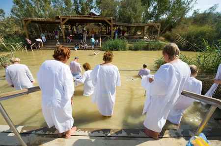 baptize: YERICHO, ISRAEL - OCT 15, 2014: Religious christians with white clothes going into the water of the Jordan river at baptismal site Qasr el Yahud near Yericho