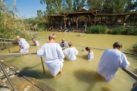 battesimo: Gerico, Israele - 15 ottobre 2014: i cristiani religiosi con abiti bianchi che entrano in acqua del fiume Giordano al sito battesimale Qasr el Yahud vicino Gerico Editoriali