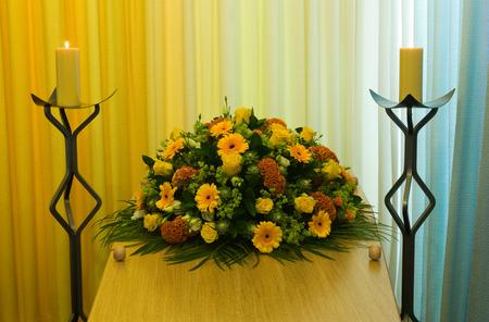 arreglo floral: Un ataúd con un arreglo de flores en una morgue con dos velas encendidas