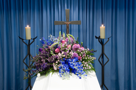 undertaker: A coffin with a flower arrangement in a morgue with two burning candles and a cross