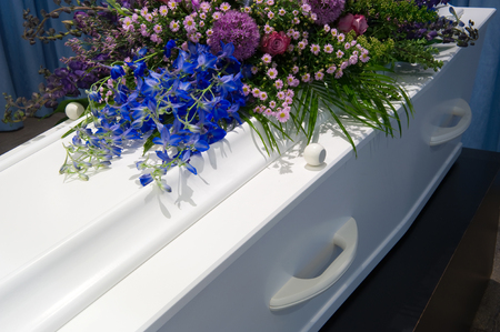 grieve: A coffin with a flower arrangement in a morgue