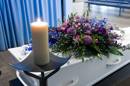A coffin with a flower arrangement in a morgue and a burning candle