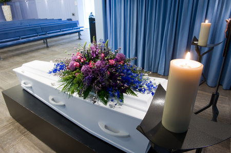 grieve: A coffin with a flower arrangement in a morgue with two burning candles Stock Photo