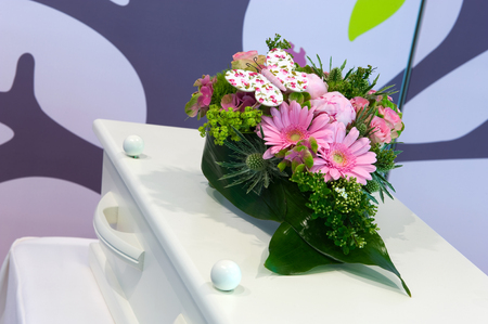 pass away: A small coffin with a flower arrangement for a child in a mortuary