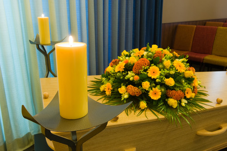 to pass away: A coffin with a flower arrangement in a morgue with two burning candles Stock Photo