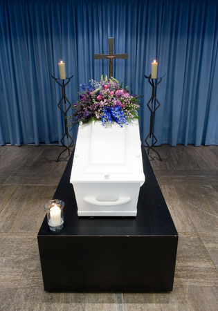 grieve: A coffin with a flower arrangement in a morgue with two burning candles and a cross