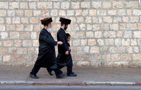 Jeruzalem, Israël - 9 oktober 2014: Twee Joodse mannen en een kind lopen op de straat een paar dagen voor Soekot of Redactioneel