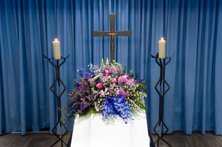 mortuary: A coffin with a flower arrangement in a morgue with two burning candles and a cross