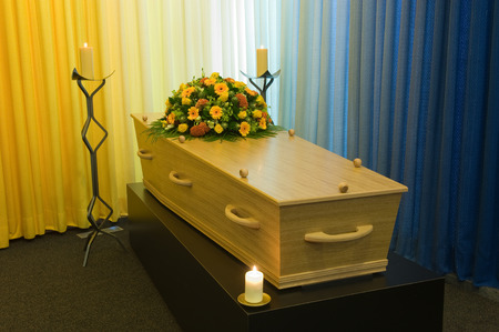 A coffin with a flower arrangement in a morgue with two burning candles Stockfoto