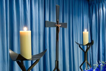 undertaker: Two burning candles and a cross in a mortuary Stock Photo