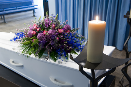 to pass away: A coffin with a flower arrangement in a morgue and a burning candle
