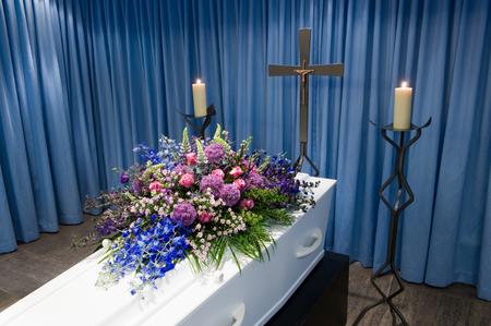 arreglo floral: Un ataúd con un arreglo de flores en una morgue con dos velas encendidas y una cruz Foto de archivo