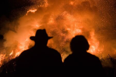 outdoor fireplace: Man with a hat and a woman are watching a huge bonfire, a tradition with easter in North-West Europe.