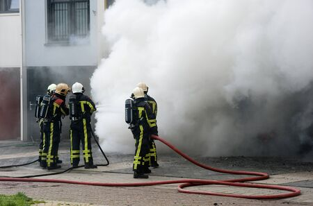 fire protection: ENSCHEDE, THE NETHERLANDS - 07 MAY, 2015: Firefighters are busy to extinguish a fire in a house