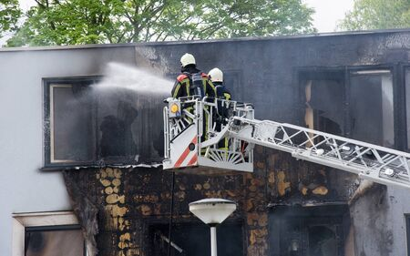 extinguish: ENSCHEDE, THE NETHERLANDS - 07 MAY, 2015: Firefighters are busy to extinguish a fire in a house on a lifting ramp Editorial