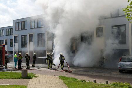 incendio casa: Enschede, Países Bajos - 07 de mayo 2015: Los bomberos están ocupados para extinguir un incendio en una casa