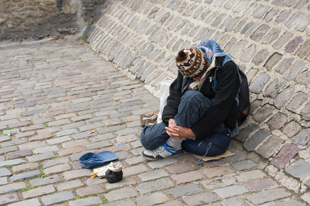 misery: PARIS, FRANCE - JULY 27, 2015: A homeless man is sitting and begging for money on a street in Paris in France