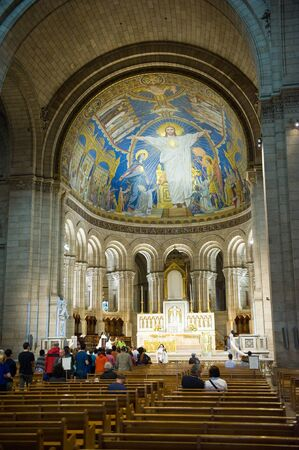 PARIS, FRANCE - JULY 27, 2015: Tourists are visiting and praying in the Sacre Coeur cathedral in Montmarte in Paris in France