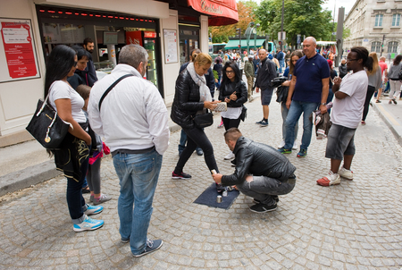 conjuring: PARIS, FRANCE - JULY 28, 2015: A man is playing a conjuring trick game what is illegal on a street in Paris in france