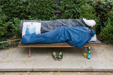 misery: PARIS, FRANCE - JULY 27, 2015: A homeless man is sleeping on a bench in a park in Paris in France
