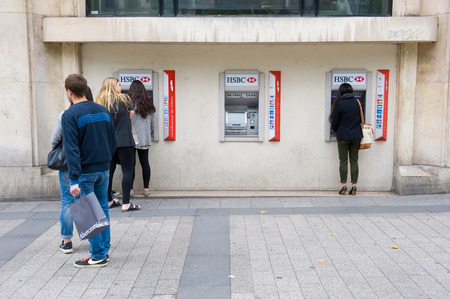 withdraw: PARIS, FRANCE - JULY 28, 2015: People waiting for an ATM machine to withdraw money on a street in Paris in France. Editorial